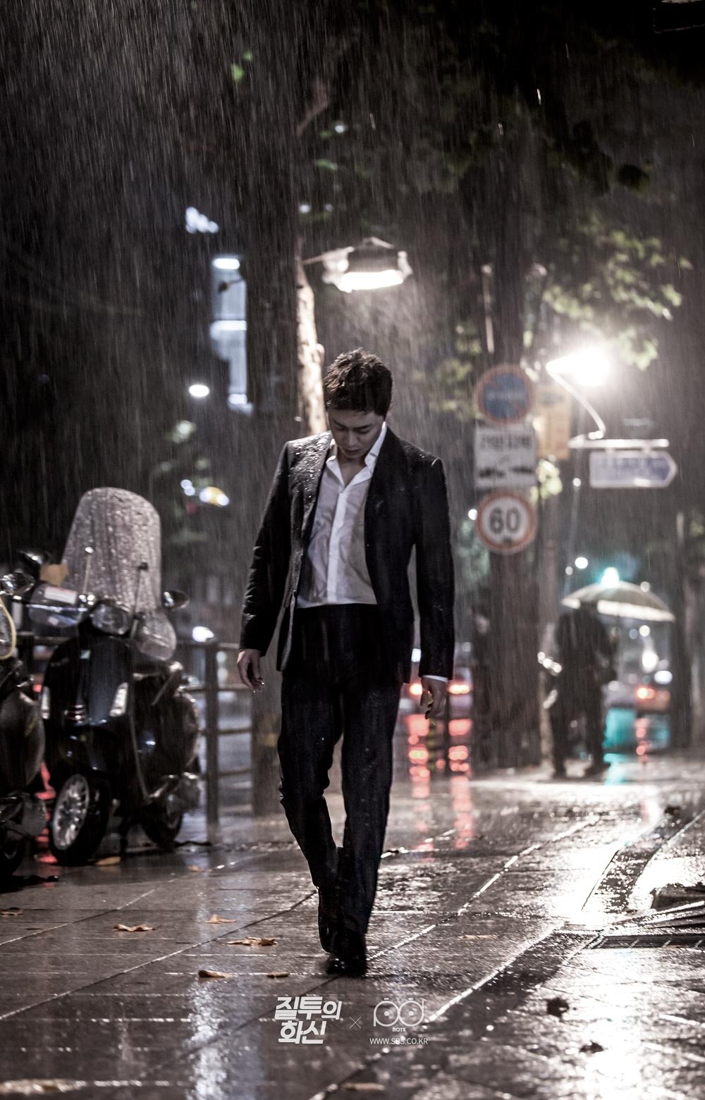 비를 맞으며 땅을 보며 슬프게 걷는 처량한 모습의 화신(조정석) 전신 사진