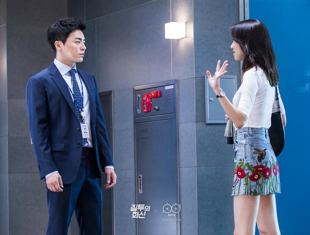 회사 엘리베이터 앞에서 만난 화신(조정석)에게 왼손을 들어 인사하는 나리(공효진)