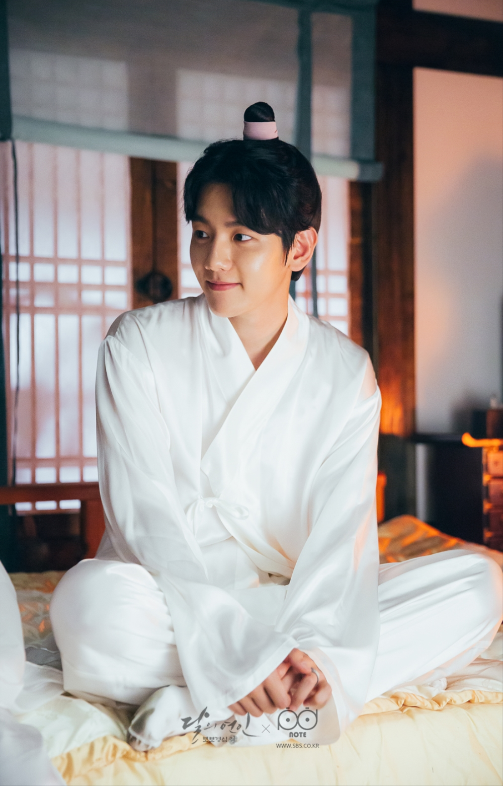 침대에 잠옷을 입고 앉아 있는 귀여운 모습의 왕은 이미지