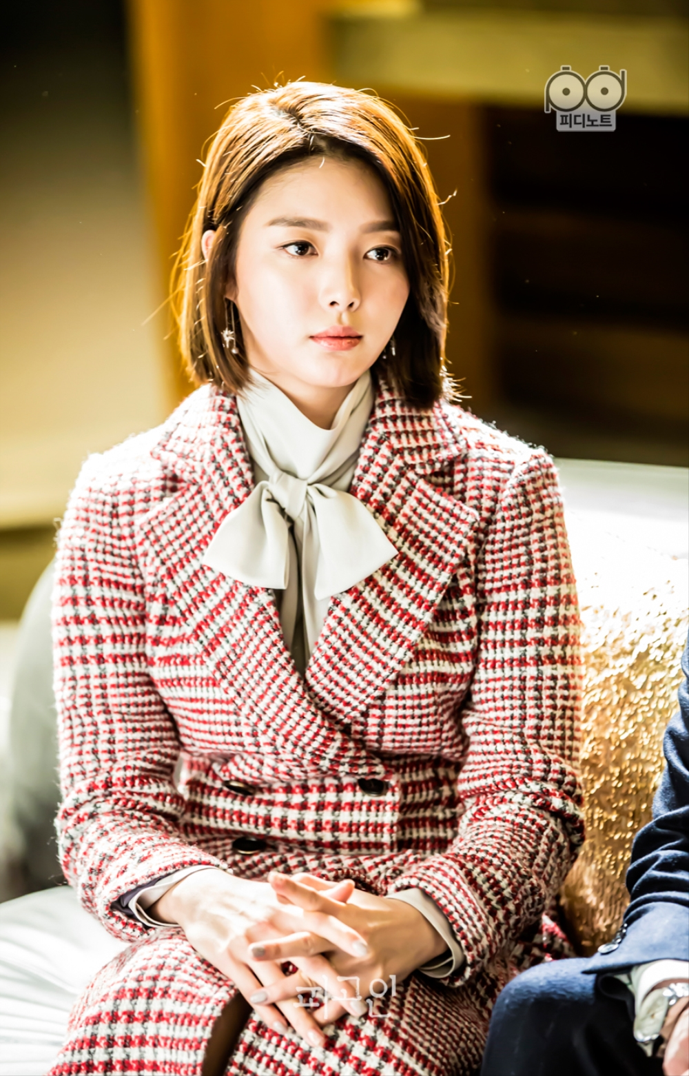 선호와 인터뷰를 하고 있는 연희의 모습. 깍지 낀 손을 무릎에 얹어 차분한 느낌으로 앉아있다.