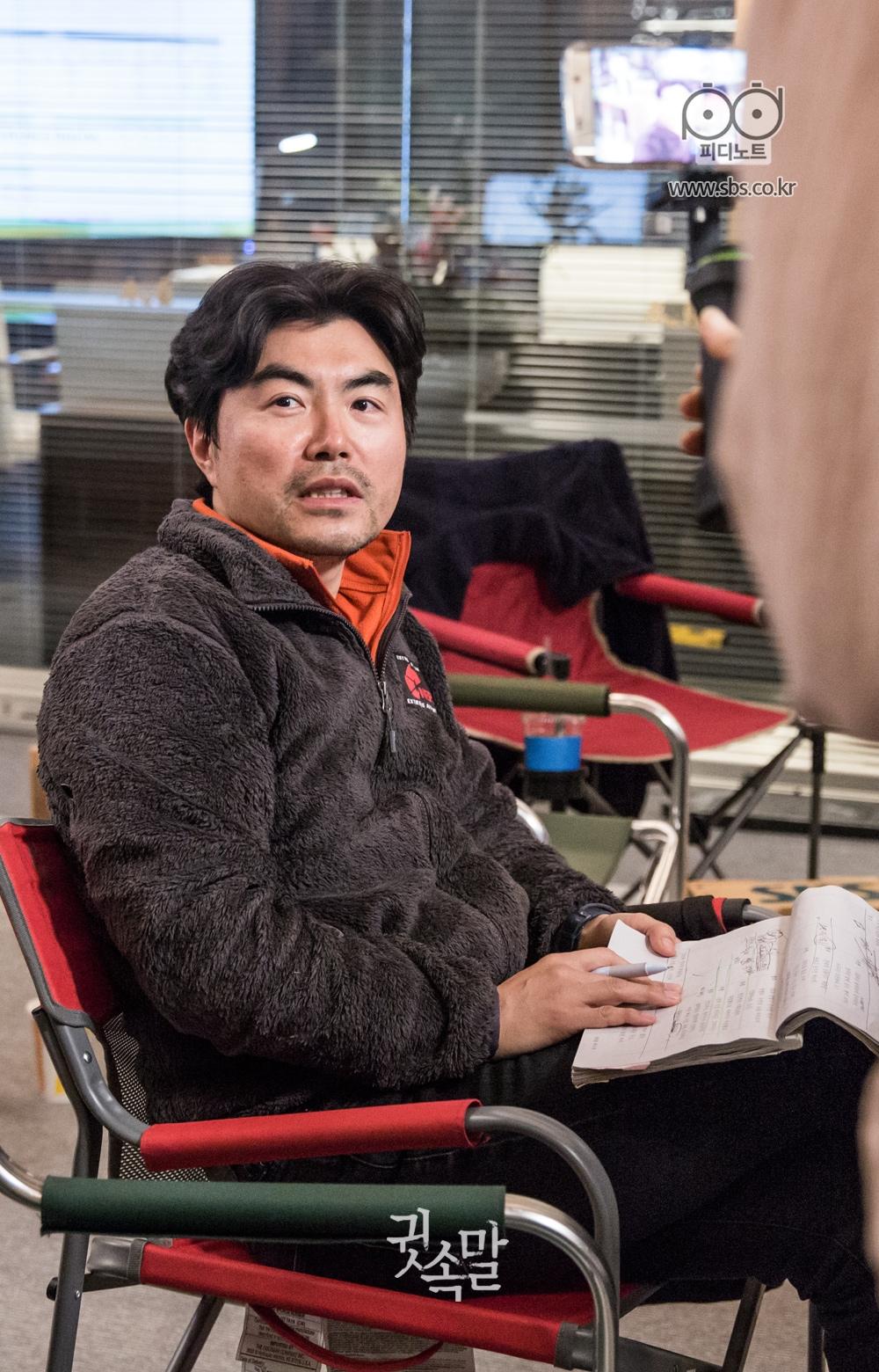 의자에 앉아 대본을 손에 들고 있는 이명우 감독님의 이미지