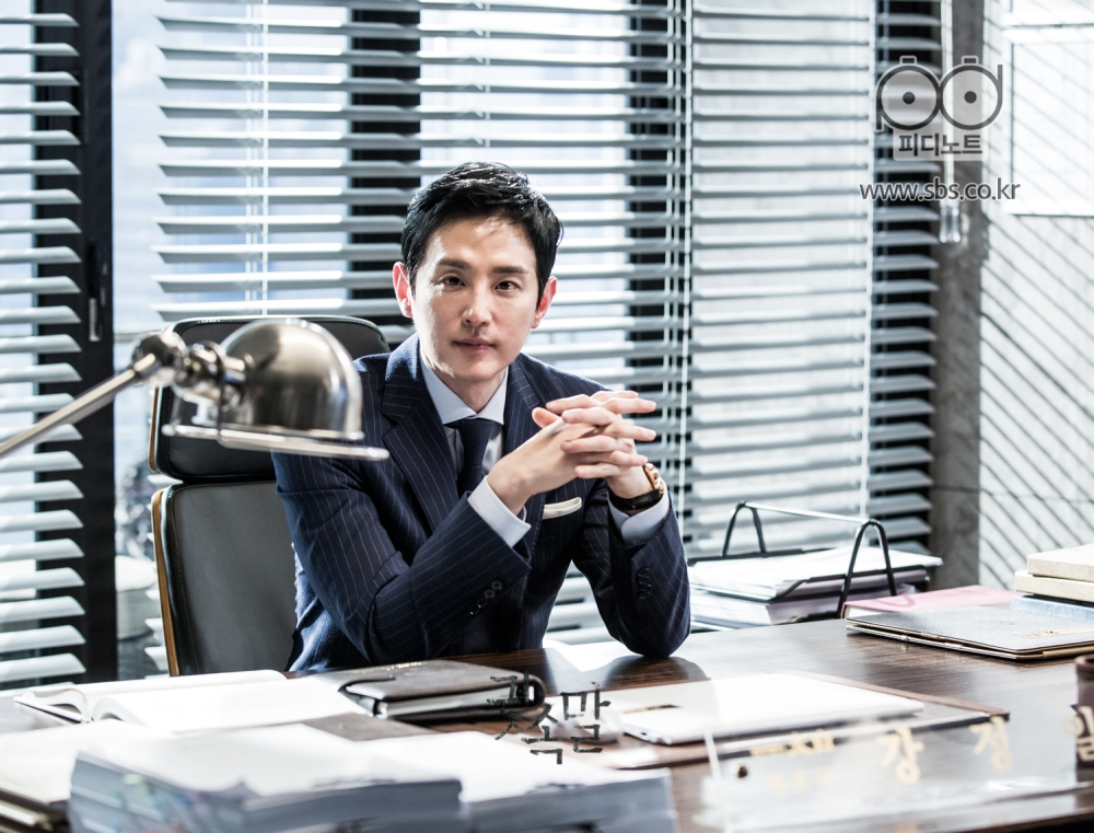 본인 집무실 책상에 앉아 카메라를 향해 바라보고 있는 정일의 이미지