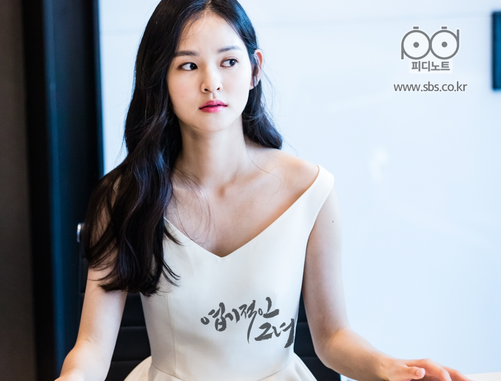 흰 드레스를 입고 검은 웨이브를 한 채, 다른 쪽으로 시선 처리를 하고 있는 청순한 모습의 김윤혜 이미지