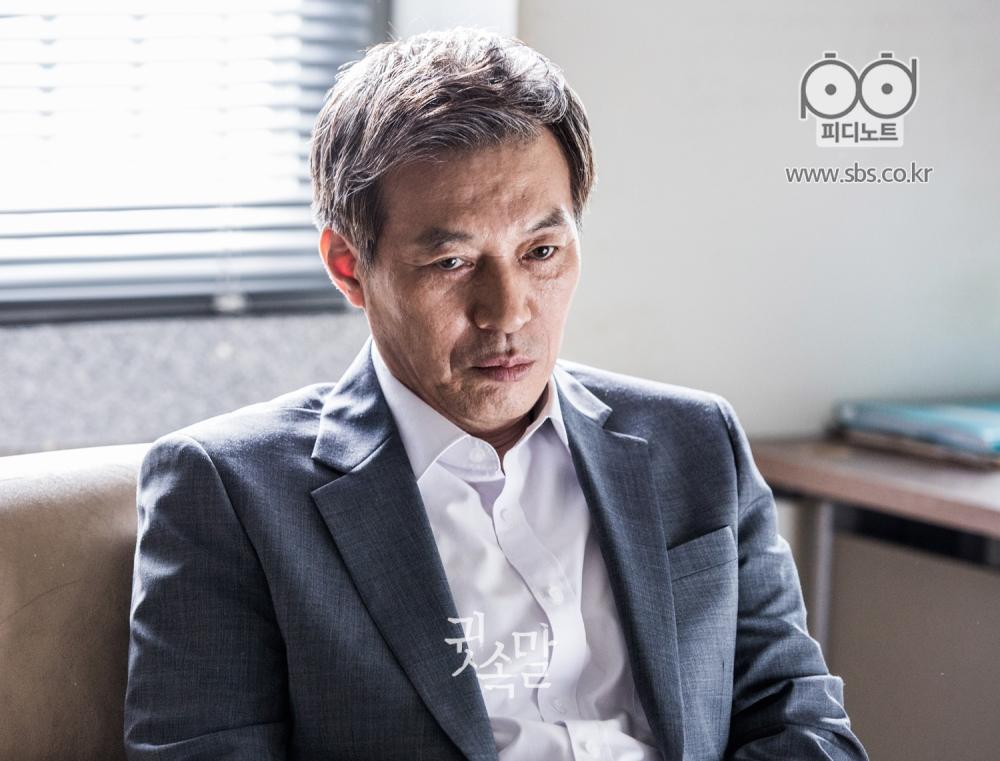 고민 가득한 표정으로 앉아 시선을 아래로 내리깔며 무언가를 생각하는 듯한 모습의 김갑수