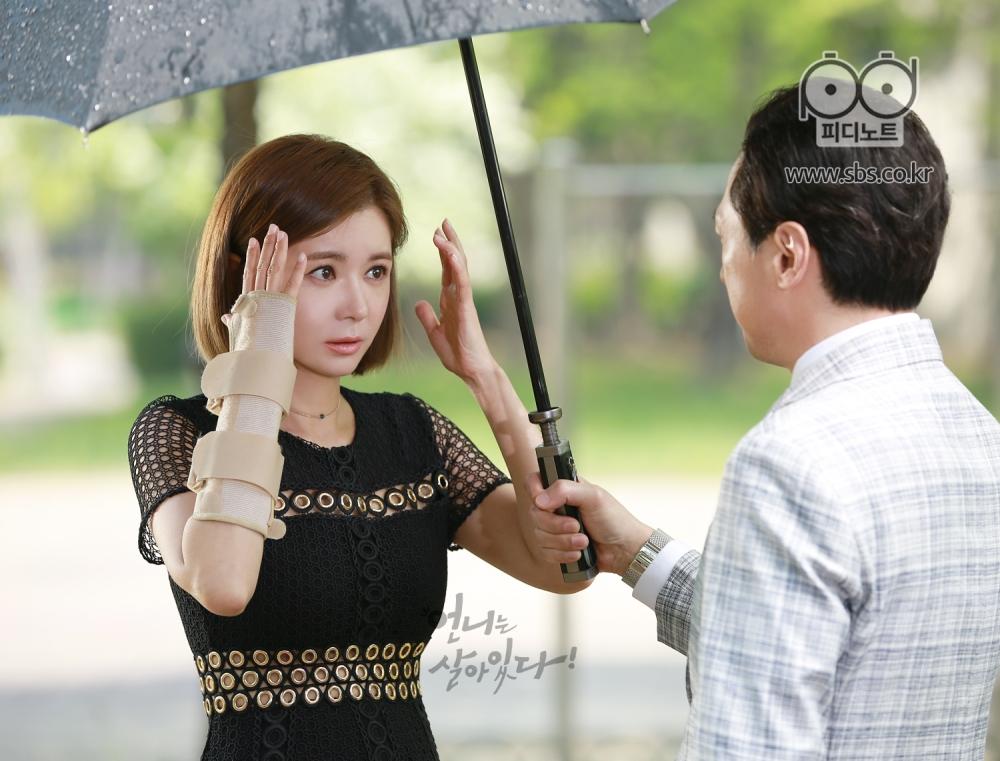 비 피하려고 손 올린 상태의 들레와 우산을 씌워주는 필모