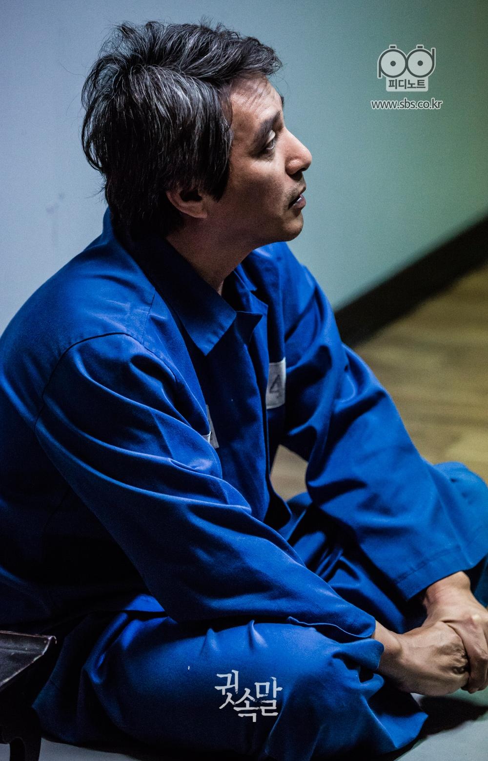 파란색 기결수복을 입고 무표정으로 앉아 있는 조재현