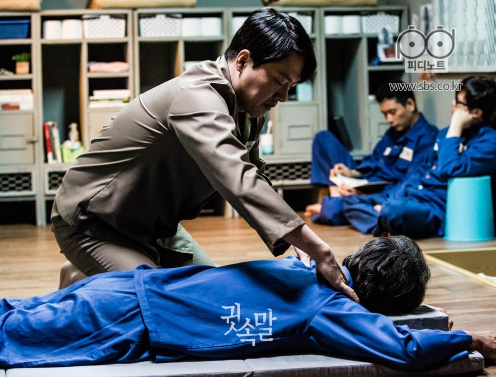 감방을 배경으로 황토색 미결수복을 입은채 파란색 기결수복을 입은 누군가의 어깨를 주무르고 있는 김형묵