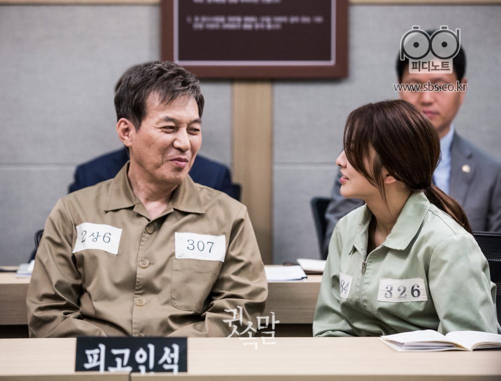 미결수복 차림으로 재판정에 나란히 앉아 미소 지으며 대화를 나누고 있는 김갑수와 박세영
