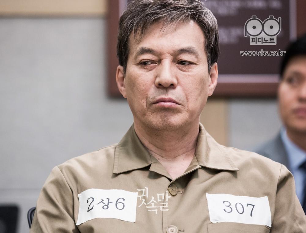 황토색 미결수복을 입은 채 재판정에 앉아있는 김갑수가 침울한 표정으로 옆을 흘겨보고 있다