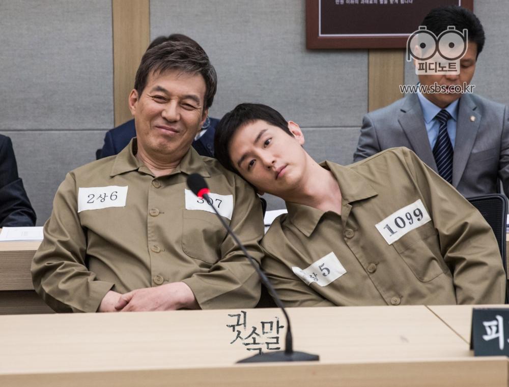 미결수복을 입은채 재판정에 앉아 미소 짓고 있는 김갑수와 김갑수의 어깨에 머리를 기댄 권율