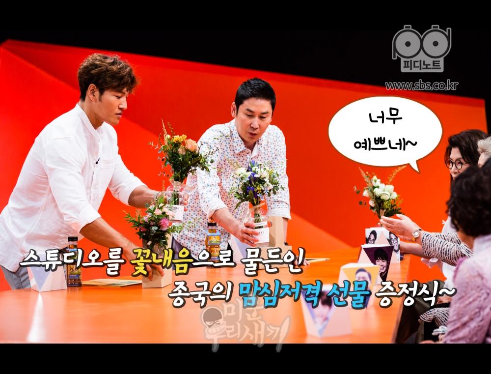 김종국이 어머니들에게 꽃을 선물 하고 있다.