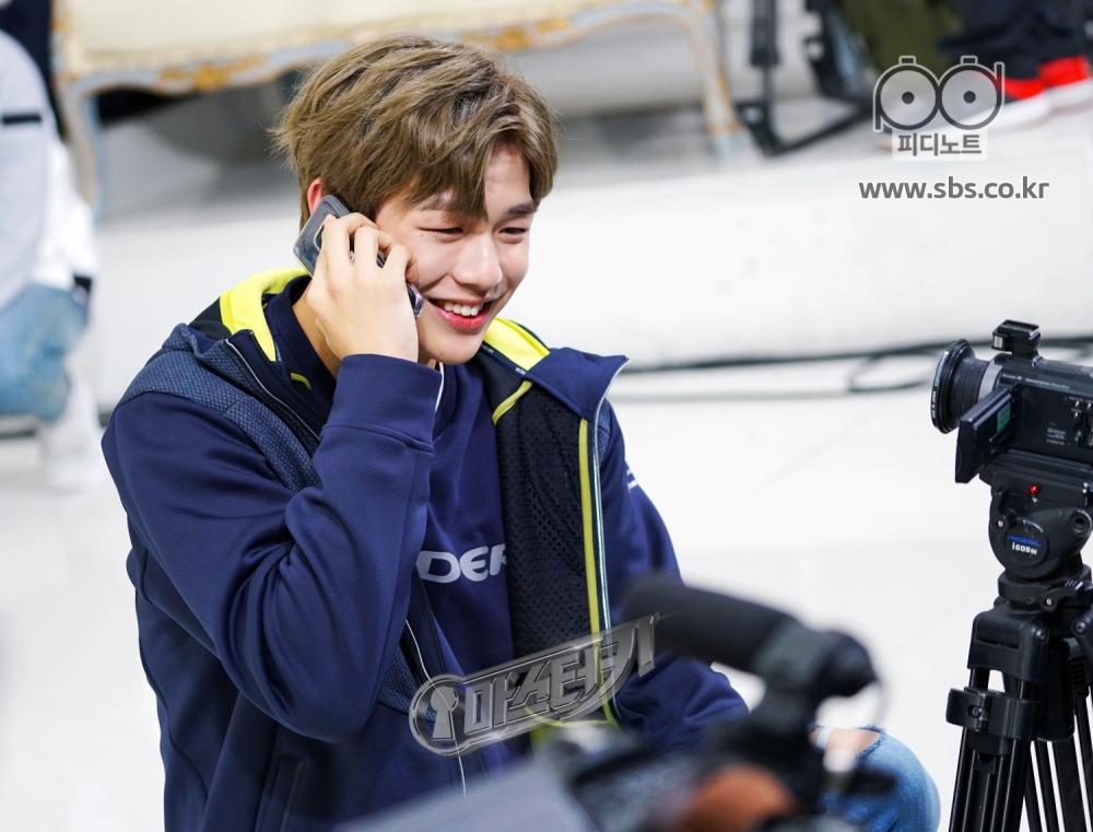 강다니엘이 전화로 흰트를 듣고 웃고있다.